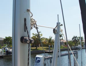 This picture shows the upper end of the MacGregor mast raising pole and the attachment to the mast of the P-23. The line from the winch on the MacGregor pole is led through the block at the tip of the pole and attaches to a ring. Also attached to the same ring are the two stabilizing stays which prevent the mast from swaying. The ring is shackled to a bail through the mast, so the one shackle connects the two baby stays and the mast raising line to the mast bail all at once.