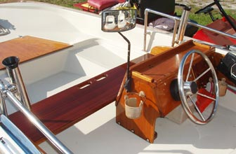 Forward bench seat with grab handle, console with rails, fishing rod holders, water ski mirror