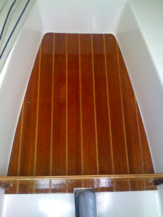 Finished teak-and-sandy sole installed in the cabin of our Sun Cat.