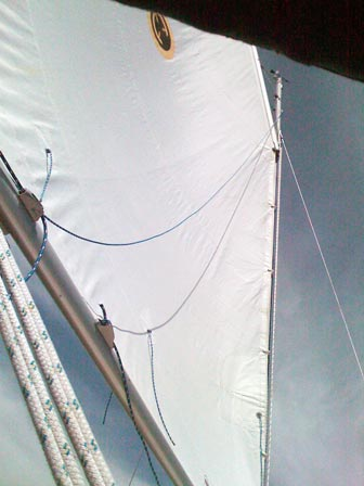 Under sail, showing slack lazy jack line and slack tack reef line